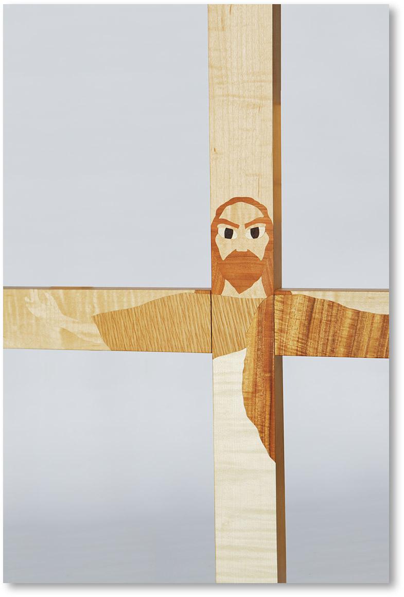 メープルの十字架にオークやチェリーを用いて図柄を表現しています。