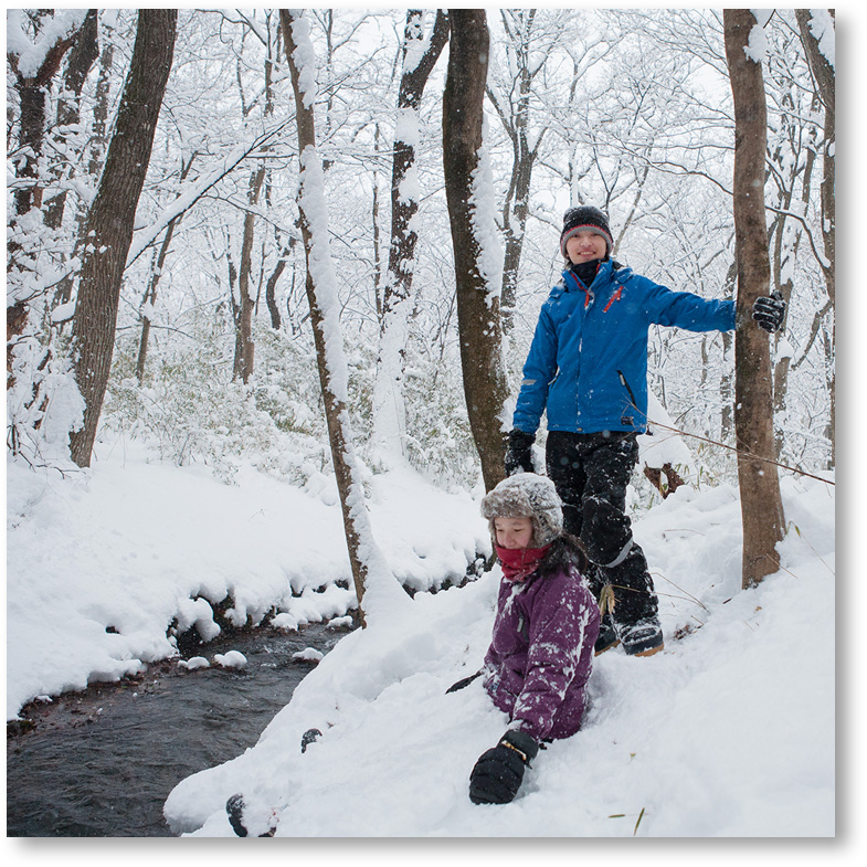 雪が降り続ける中で遊ぶ子供たち